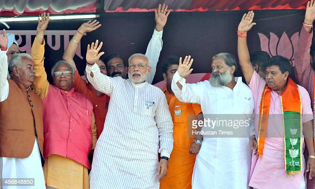 Prime Minister Narendra Modi greets supporters during an election campaign rally on October 8 2014 in Jagadhri India Haryana Legislative Assembly...