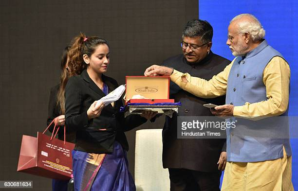 Prime Minister Narendra Modi making payment through the newly launched mobile app 'BHIM' for a Khadi product as Union IT Minister Ravishankar Prasad...