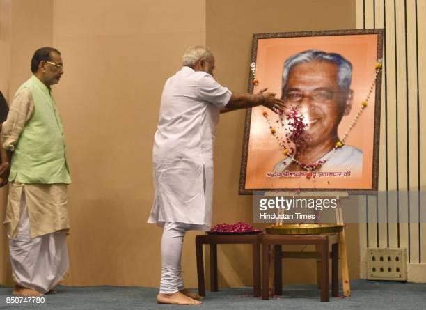 Prime Minister Narendra Modi pays floral tribute to the portrait of Laxman Rao Inamdar during his birth centenary celebration and Sahakar Sammelan on...
