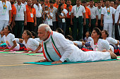 Prime Minister Narendra Modi performs yoga along with others at Rajpath during mass yoga session to mark the International Day of Yoga on June 21...