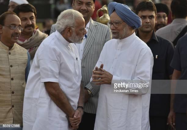Prime Minister Narendra Modi talks to former PM Manmohan Singh during the Dussehra festival celebration organised by Shri Dharmik Leela Committee at...