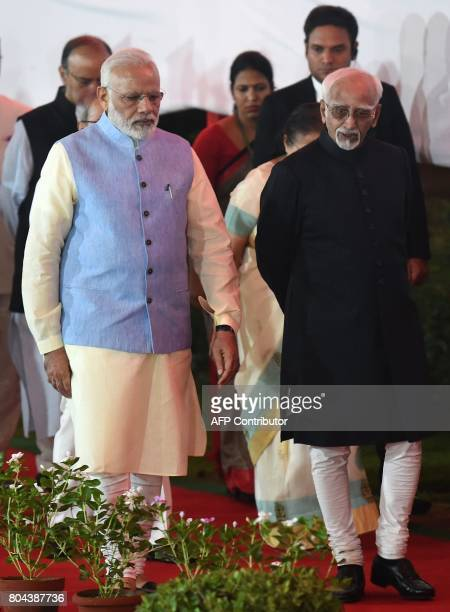 Prime Minister Narendra Modi talks with VicePresident Hamid Ansari as they arrive for a special session for the implementation of The Goods and...