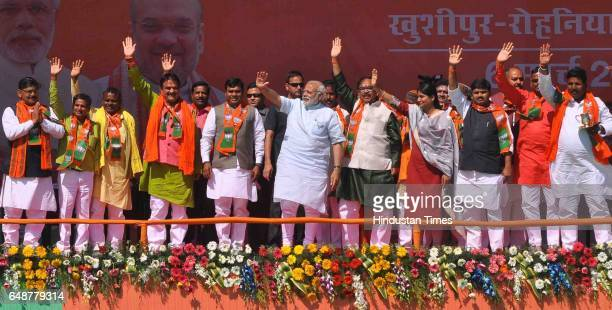 Prime Minister Narendra Modi waves at the crowd during a visit to Khushipur on March 6 2017 in Varanasi India For the last three days PM Modi has...