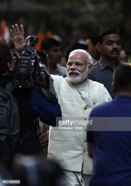 Prime Minister Narendra Modi waves to his supporters while heading towards BJP headquarters to celebrate party landslide victory in assembly...