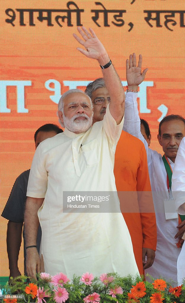 Prime Minister Narendra Modi waving at the crowd at a rally to mark the second anniversary of the formation of his government at the centre, on May 26, 2016 in Saharanpur, India. Prime Minister Narendra Modi's speech to mark two years of his government focused on farmers and the poor at a massive rally in Saharanpur in Uttar Pradesh, where crucial assembly elections will be held early next year.
