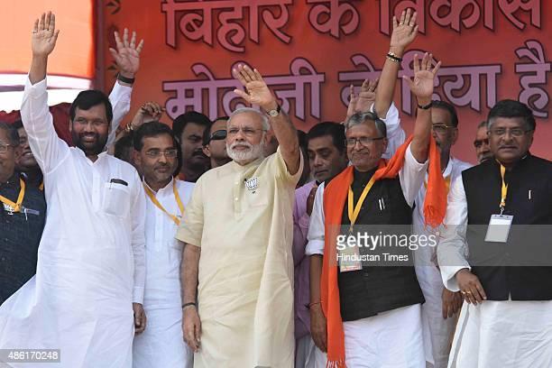 Prime Minister Narendra Modi with LJP leader Ram Vilas Paswan BJP leaders Sushil Kumar Modi and Ravi Shankar Prasad waves to public during his rally...