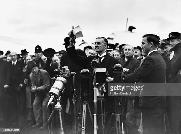 Prime Minister Neville Chamberlain waves to the crowd at Heston Airport and declaims 'Peace in our Time' after returning from signing the Munich...