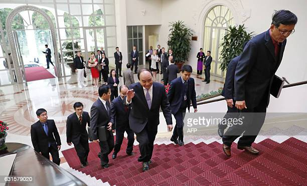 Prime Minister Nguyen Xuan Phuc waves as he enters for a meeting with US Secretary of State John Kerry at the Office of the Government before their...