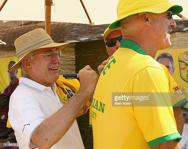 Prime Minister of Australia John Howard signs the back of the shirt worn by former Australian fast bowler Dennis Lillie before play in the third...
