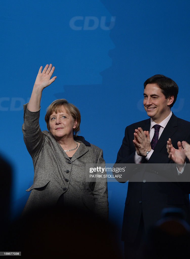 Prime Minister of German Federal State, Lower-Saxony, David McAllister (R) reacts next to German Chancellor Angela Merkel after a speech during an election campaign event of the regional Christian Democratic Union party for 2013 state elections in Osnabrueck, northern Germany, on January 16, 2013. McAllister started his election campaign to keep his post as Lower Saxony's State Premier after regional elections on January 20, 2013. AFP PHOTO / PATRIK STOLLARZ
