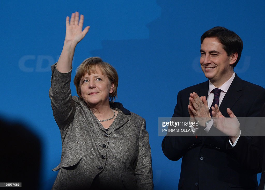 Prime Minister of German Federal State, Lower-Saxony, David McAllister (R) reacts next to German Chancellor Angela Merkel after a speech during an election campaign event of the regional Christian Democratic Union party for 2013 state elections in Osnabrueck, northern Germany, on January 16, 2013. McAllister started his election campaign to keep his post as Lower Saxony's State Premier after regional elections on January 20, 2013.