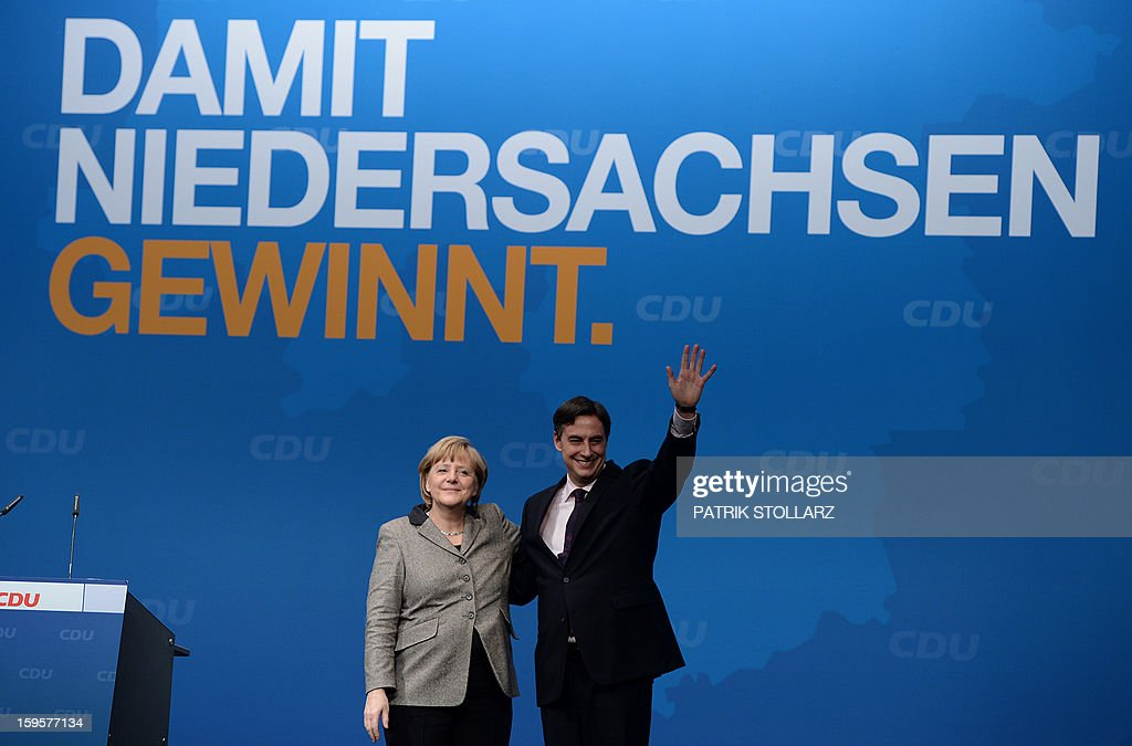 Prime Minister of German Federal State, Lower-Saxony, David McAllister (R) waves next to German Chancellor Angela Merkel after a speech during an election campaign event of the regional Christian Democratic Union party for 2013 state elections in Osnabrueck, northern Germany, on January 16, 2013. McAllister started his election campaign to keep his post as Lower Saxony's State Premier after regional elections on January 20, 2013.