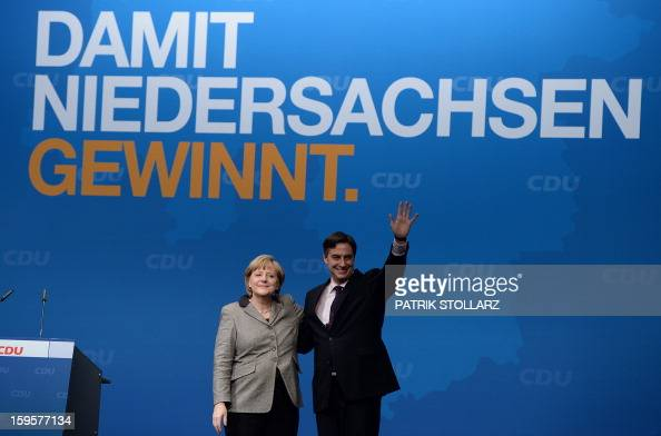 Prime Minister of German Federal State LowerSaxony David McAllister waves next to German Chancellor Angela Merkel after a speech during an election...