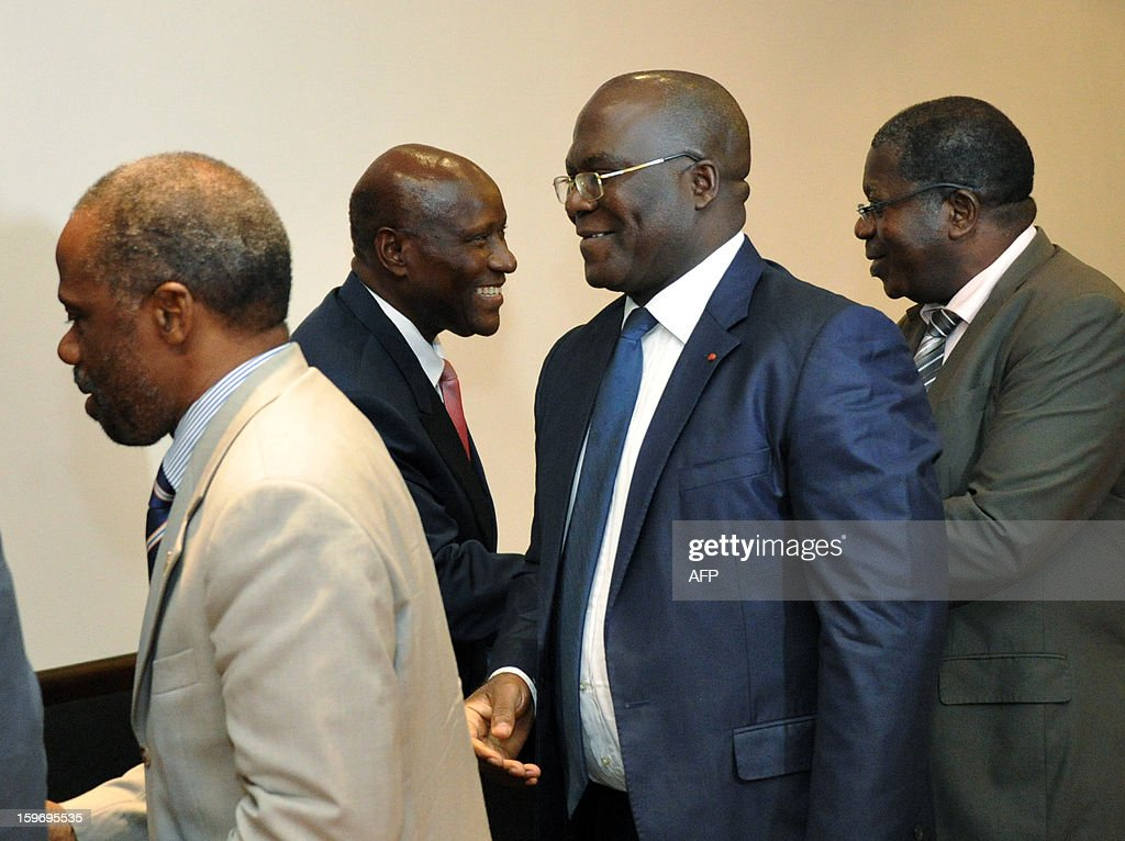 Prime Minister of Ivory Coast Daniel Kablan Duncan (2ndL) shakes hands with leaders of ex-president Laurent Gbagbo's Ivorian Popular Front (FPI) party, FPI's interim president Sylvain Miaka Oureto (R), Michel Amani N'guessan (2ndR) and Danon Djedje (L), on January 18, 2013 prior to a meeting at the Prime Minister office in Abidjan.