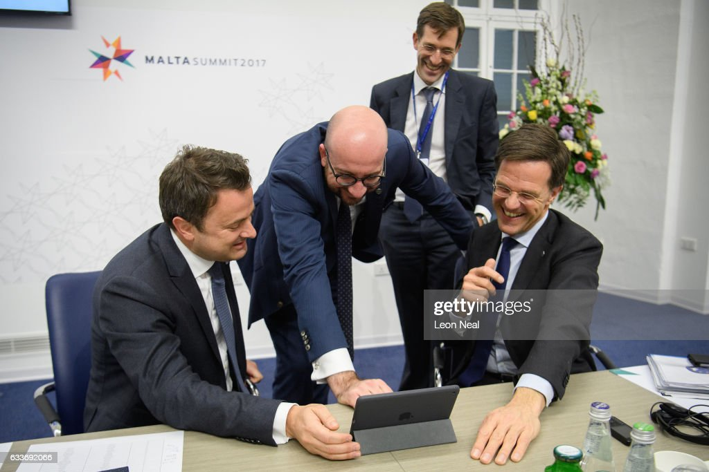 Prime Minister of Luxembourg Xavier Bettel (L), Prime Minister of Belgium Charles Michel (2L) and Prime Minister of the Netherlands Mark Rutte (R) laugh as they watch a satirical sketch from the satirical tv show 'Wat Als?', titled 'What if everyone forgot about Luxembourg?' ahead of a round table meeting at the EU Informal Summit on February 3, 2017 in Valletta, Malta. Theresa May attends an informal summit of the 27 EU leaders to brief them on her recent meeting with President Trump. She has secured a guarantee from Trump that he is 100% supportive of NATO and she will encourage the EU countries to contribute the agreed 2% of their GDP on defence.