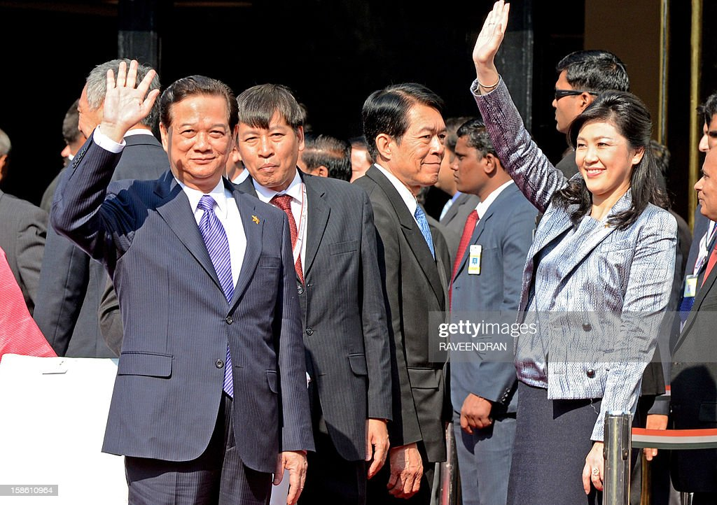 Prime Minister of Thailand Yingluck Shinawatra (R) and Vietnam Prime Minister Nguyen Tan Dung wave during the ASEAN flag down ceremony in New Delhi on December 21, 2012. The leaders arrived in Delhi for the India-Association of Southeast Asian Nations (India-ASEAN) summit held from December 20-21. AFP PHOTO/ RAVEENDRAN