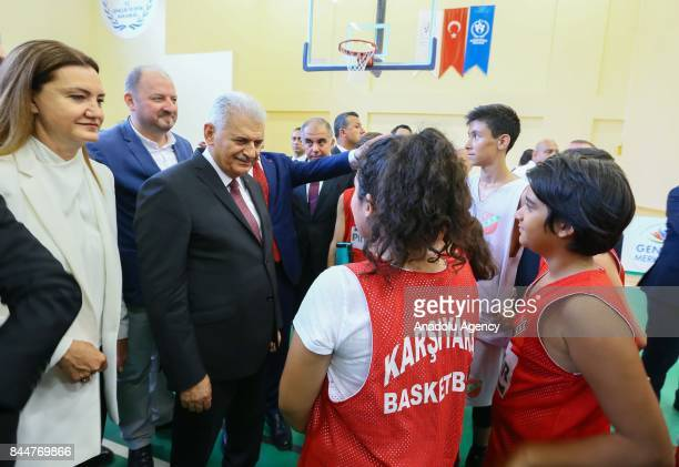 Prime Minister of Turkey Binali Yildirim greets a girl after the opening ceremony of Buca Yasin Boru Youth Centre and groundbreaking ceremony of...