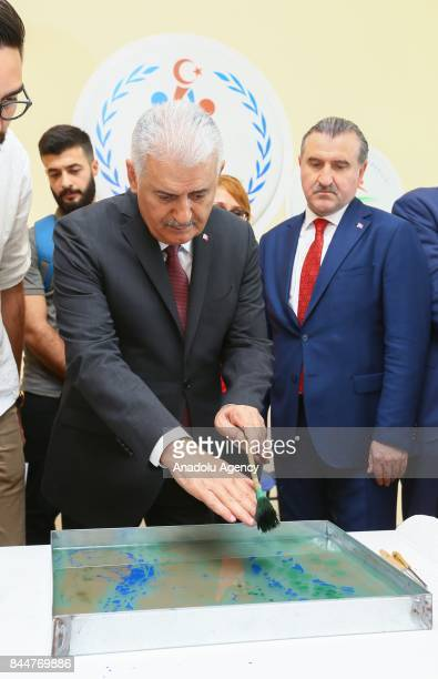 Prime Minister of Turkey Binali Yildirim paints Turkish paper marbling after the opening ceremony of Buca Yasin Boru Youth Centre and groundbreaking...