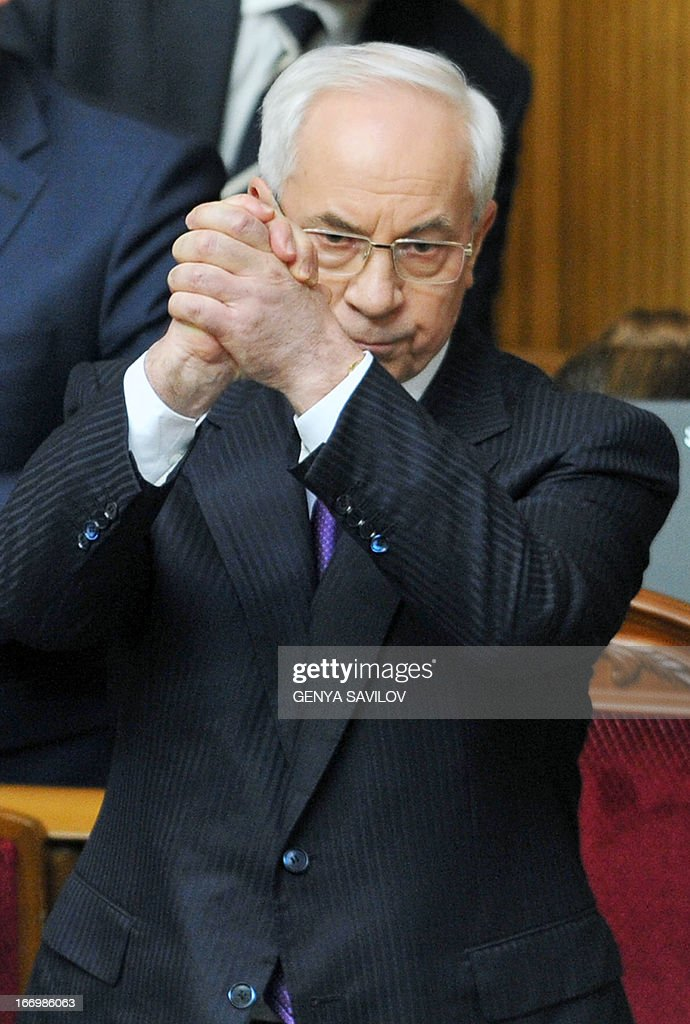 Prime Minister of Ukraine Mykola Azarov (C) raises his hands in Kiev on April 19, 2013. A vote of no confidence in the government initiated by opposition deputies did not achieve the necessary majority. SAVILOV
