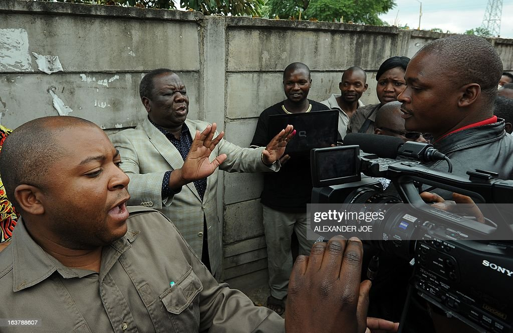 Prime Minister of Zimbabwe Morgan Tsvangirai (2ndL) gestures as he addresses the media after casting his vote in Saint-Marys on March 16, 2013, as voting kicked off for Zimbabweans referendum to adopt a new charter to pave way for new elections and a possible end to a shaky power-sharing government.