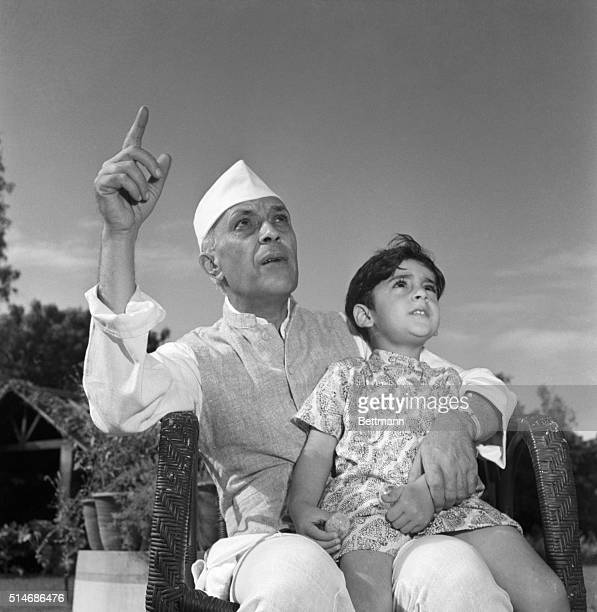 Prime Minister Pandit Jawaharlal Nehru tells his grandson Rajiva Gandhi a story in the family garden