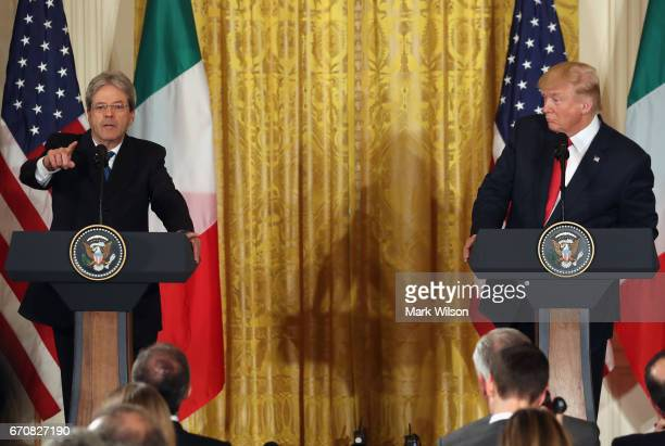 Prime Minister Paolo Gentiloni of Italy takes a question from a reporter as US President Donald Trump looks on during a news conference in the East...