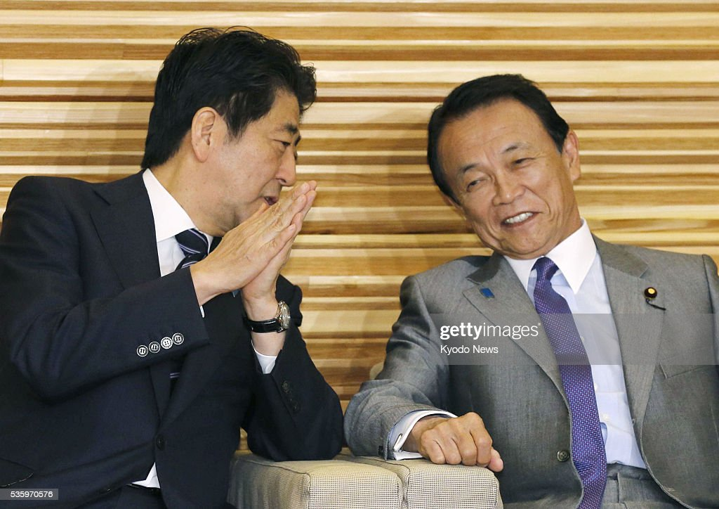 Prime Minister Shinzo Abe (L) and Finance Minister Taro Aso chat before a Cabinet meeting in Tokyo on May 31, 2016. During their meeting the previous night, Aso accepted Abe's plan to postpone a consumption tax hike by two and a half years from April 2017. Aso had initially opposed the postponement.