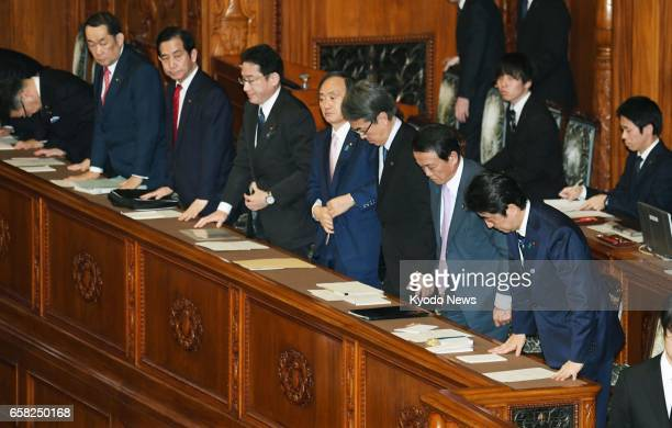 Prime Minister Shinzo Abe and his Cabinet ministers bow during the upper house plenary session in Tokyo on March 27 as the parliament enacted a...