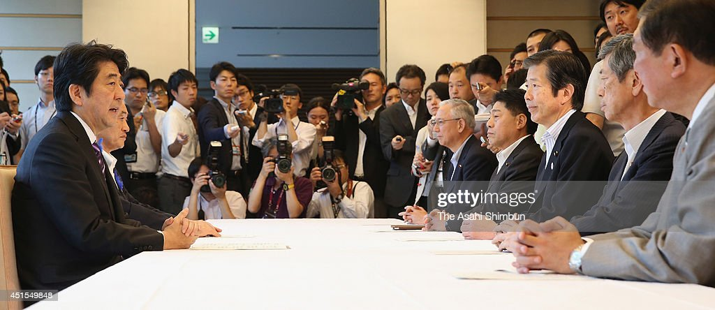 Prime Minister <a gi-track='captionPersonalityLinkClicked' href=/galleries/search?phrase=Shinzo+Abe&family=editorial&specificpeople=559017 ng-click='$event.stopPropagation()'>Shinzo Abe</a> (1st L) listens to the explanation from junior coalition New Komeito leader <a gi-track='captionPersonalityLinkClicked' href=/galleries/search?phrase=Natsuo+Yamaguchi&family=editorial&specificpeople=5718603 ng-click='$event.stopPropagation()'>Natsuo Yamaguchi</a> (3rd R) at his official residence on July 1, 2014 in Tokyo, Japan. Prime Minister <a gi-track='captionPersonalityLinkClicked' href=/galleries/search?phrase=Shinzo+Abe&family=editorial&specificpeople=559017 ng-click='$event.stopPropagation()'>Shinzo Abe</a>'s Cabinet approved changes to Japan's postwar security policy that could lead to the Self-Defense Forces' use of military force in overseas battles. The Cabinet approved a document that revises the government's interpretation of war-renouncing Article 9 of the Constitution to allow Japan to exercise the right to collective self-defense.