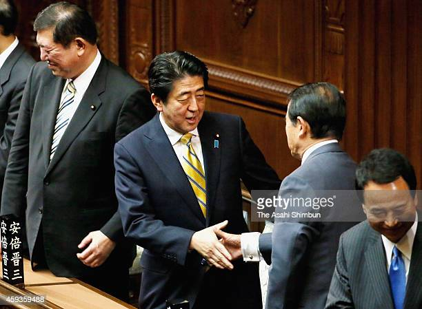 Prime Minister Shinzo Abe shakes hands with Finance Minister Taro Aso after the diet was dissolved at the diet building on November 21 2014 in Tokyo...