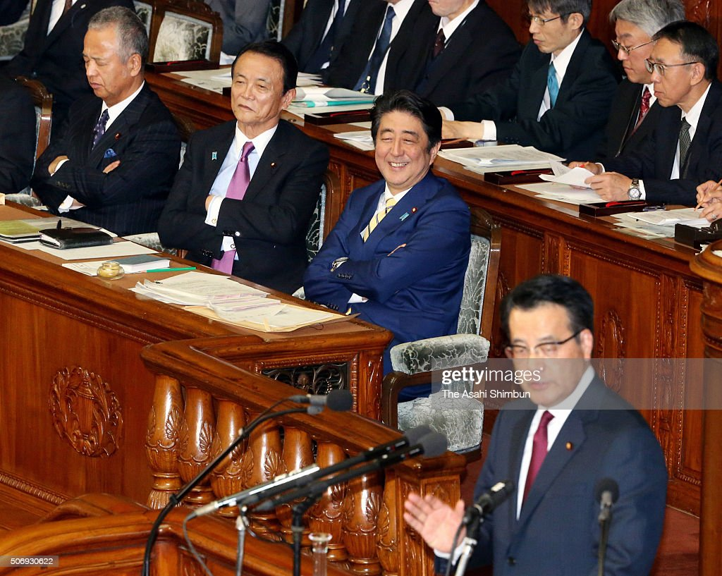 Prime Minister <a gi-track='captionPersonalityLinkClicked' href=/galleries/search?phrase=Shinzo+Abe&family=editorial&specificpeople=559017 ng-click='$event.stopPropagation()'>Shinzo Abe</a> smiles while opposition Democratic Party of Japan President <a gi-track='captionPersonalityLinkClicked' href=/galleries/search?phrase=Katsuya+Okada&family=editorial&specificpeople=226520 ng-click='$event.stopPropagation()'>Katsuya Okada</a> addresses during the party leaders question at a plenary session of the lower house at the diet building on January 26, 2016 in Tokyo, Japan. The scandal involving Akira Amari, a prominent member of Abe's Cabinet sent opposition parties on the offensive. Opposition parties are pursuing Abe's responsibility for appointing Amari.