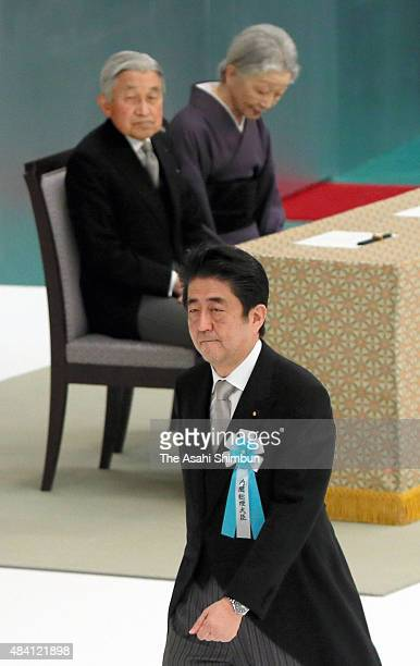 Prime Minister Shinzo Abe walks on stage past Emperor Akihito and Empress Michiko to address during the memorial service at the Nippon Budokan on the...