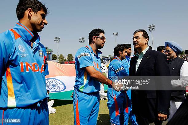 Prime Minister Syed Yusuf Raza Gilani of Pakistan shakes hands with Yuvraj Singh of India as Prime Minister Manmohan Singh of India looks on prior to...