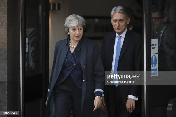 Prime Minister Theresa May and Chancellor of the Exchequer Phillip Hammond leave the Midland Hotel at the start of day two of the Conservative Party...