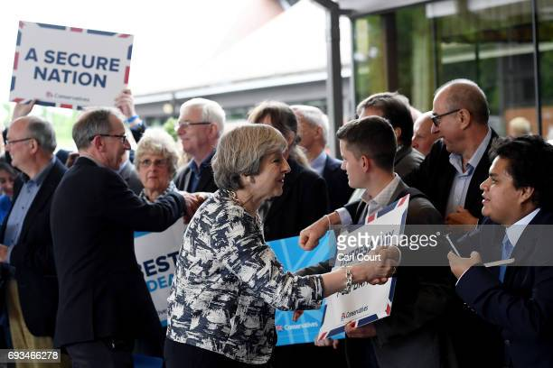 Prime Minister Theresa May greets supporters with her husband Philip as she arrives for her last campaign visit at the National Conference Centre on...
