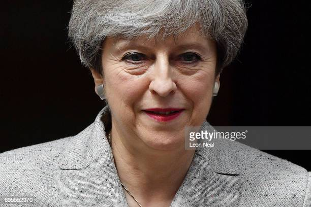 Prime Minister Theresa May leaves after meeting DUP leader Arlene Foster at 10 Downing Street on June 13 2017 in London England Discussions between...