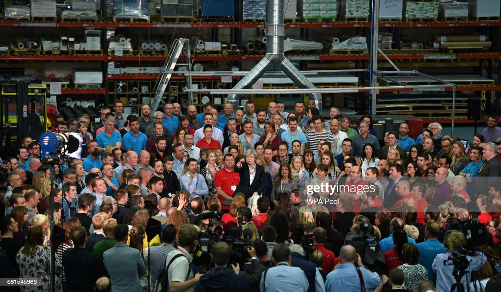Prime Minister Theresa May (C) points as she speaks to an assembled crowd during a general election campaign event at marketing services group Linney on May 10, 2017 in Scunthorpe, England. Campaigning is underway ahead of the general election which is to be held on June 8th.