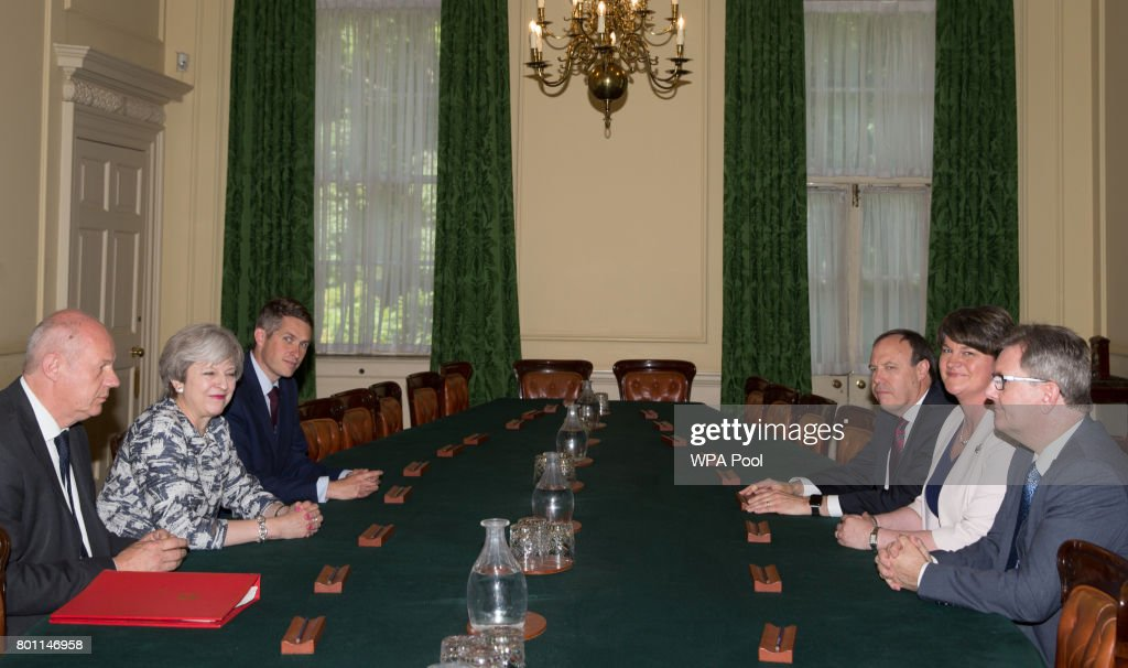 Prime Minister Theresa May (2L) sits with First Secretary of State Damian Green (L), and Parliamentary Secretary to the Treasury, and Chief Whip, Gavin Williamson (3L) as they talk with Democratic Unionist Party (DUP) leader Arlene Foster (2R), DUP Deputy Leader Nigel Dodds (3R), and DUP MP Jeffrey Donaldson, inside 10 Downing Street on June 26, 2017 in London, England. Prime Minister Theresa May's Conservatives signed a deal Monday with Northern Ireland's Democratic Unionist Party that will allow them to govern after losing their majority in a general election this month.