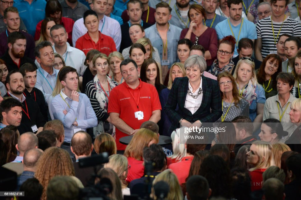 Prime Minister Theresa May (C) speaks to an assembled crowd during a general election campaign event at marketing services group Linney on May 10, 2017 in Mansfield, England. Campaigning is underway ahead of the general election which is to be held on June 8th.
