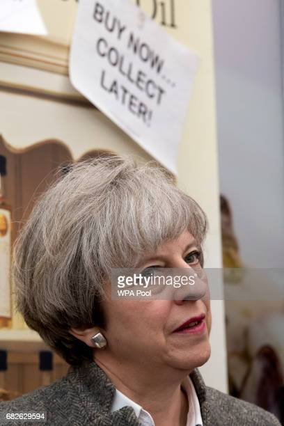Prime Minister Theresa May speaks with stall holders as she walks around at the Balmoral Show during a general election campaign visit on May 13 in...