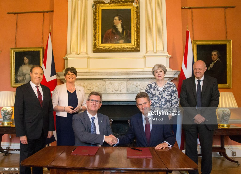 Prime Minister Theresa May (2R) stands with First Secretary of State Damian Green (R), Democratic Unionist Party (DUP) leader Arlene Foster (2L), DUP Deputy Leader Nigel Dodds (L), as DUP MP Jeffrey Donaldson (3L) shakes hands with Parliamentary Secretary to the Treasury, and Chief Whip, Gavin Williamson, inside 10 Downing Street on June 26, 2017 in London, England. Prime Minister Theresa May's Conservatives signed a deal Monday with Northern Ireland's Democratic Unionist Party that will allow them to govern after losing their majority in a general election this month.