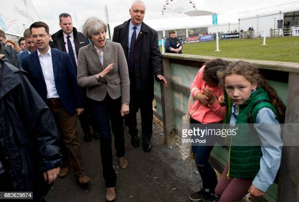 Prime Minister Theresa May waves at children as she walks around outside at the Balmoral Show during a general election campaign visit on May 13 in...