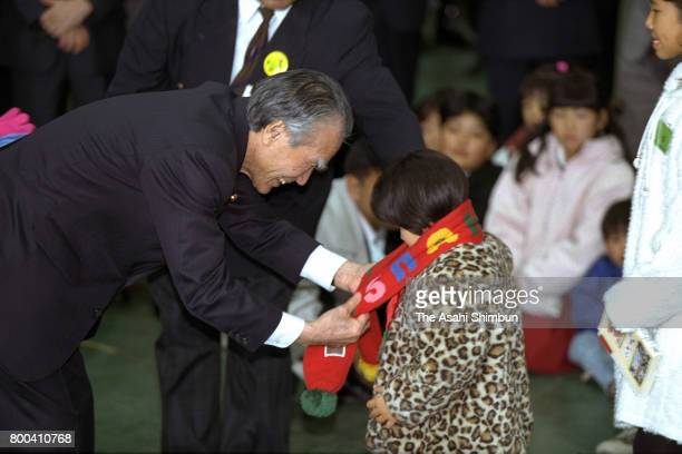 Prime Minister Tomiichi Murayama presents a scarf to a children who lost her parents at the Great Hanshin Earthquake on December 17 1995 in Kobe...