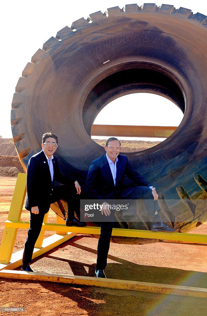 Prime Minister Tony Abbott (R) and Japanese Prime Minister Shinzo Abe pose for a photograph next to a haulage truck tyre during a tour of the Rio Tinto West Angelas iron ore mine in the Pilbara on July 9, 2014 in the Pilbara, West Australia. The Japanese Prime Minister is in Australia for three days and will sign a Economic Partnership Agreement with Australia. Japan is Australia's second biggest trading partner.
