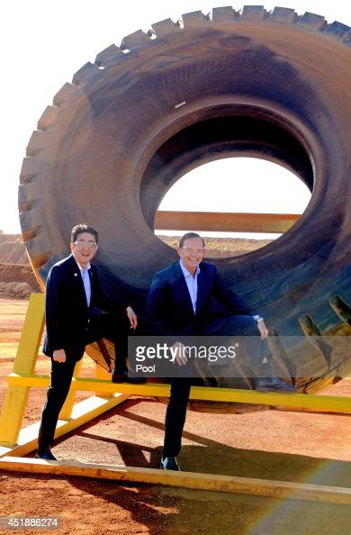 Prime Minister Tony Abbott and Japanese Prime Minister Shinzo Abe pose for a photograph next to a haulage truck tyre during a tour of the Rio Tinto...