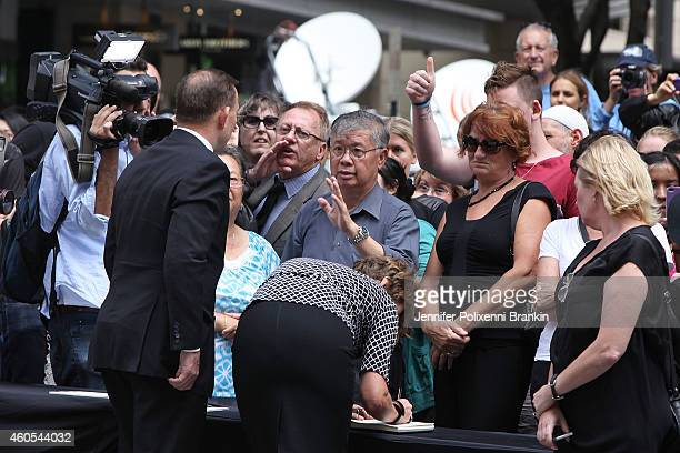 Prime Minister Tony Abbott gets heckled by members of the public while signing the condolence book on December 16 2014 in Sydney Australia Sydney...