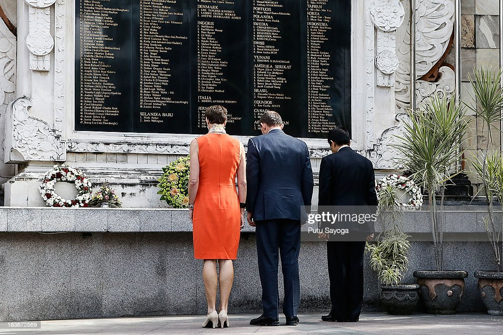 Prime Minister Tony Abbott (C), his wife Maggie Abbott (L) and Bali's Governor Made Mangku Pastika prays at the Bali bombing memorial site on October 9, 2013 in Kuta, Indonesia. Mr Abbott has announced the Victims of Overseas Terrorism Compensation Scheme will now include attacks dating back to September 10, 2001.