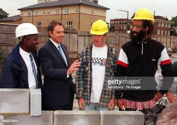 Prime Minister Tony Blair talks to a group of construction workers on the Holly Street Estate in Hackney East London today prior to the launch of the...