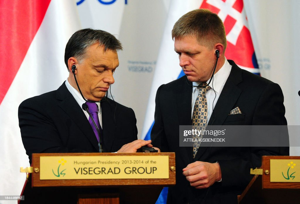Prime minister Viktor Orban (L) of Hungary adjusts an earphone of his counterpart Robert Fico (R) of Slovakia during a joint press conference in Delegation Hall of the parliament building in Budapest on October 14, 2013 after their official talks of Prime Ministers of the Visegrad contries (V4).