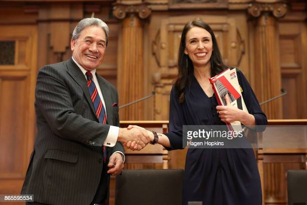 Prime Ministerdesignate Jacinda Ardern and NZ First leader Winston Peters shake hands during a coalition agreement signing at Parliament on October...